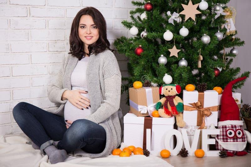 Glückliche junge schwangere Frau mit Weihnachtsbaum stockfoto