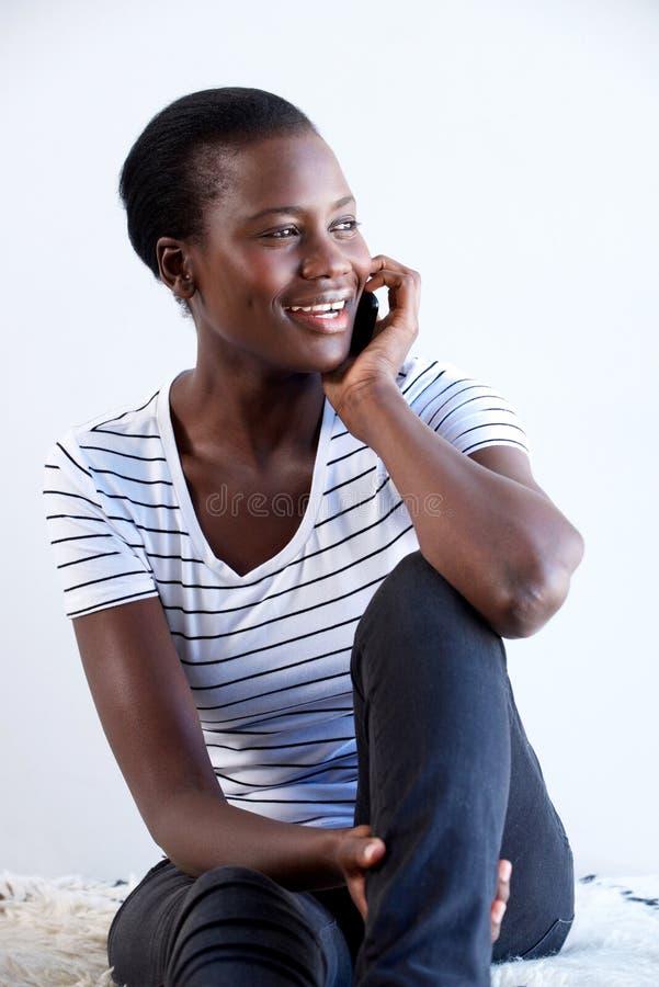 Glückliche junge schwarze Frau, die zuhause sitzt und am Handy spricht lizenzfreie stockbilder
