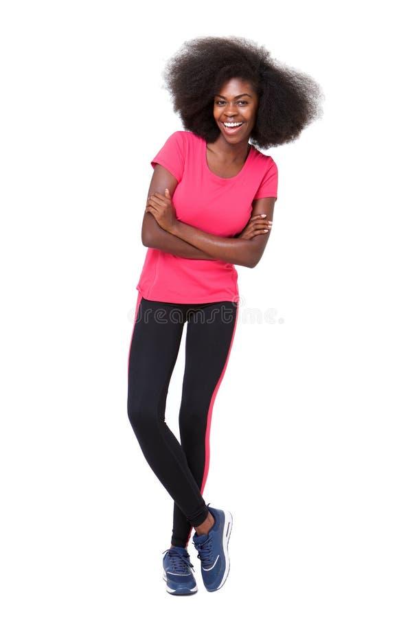 Glückliche junge schwarze Sportfrauenstellung gegen lokalisierten weißen Hintergrund lizenzfreie stockfotografie