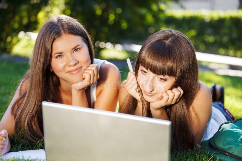 Glückliche junge Studentenmädchen, die draußen einen Computer verwenden lizenzfreies stockfoto