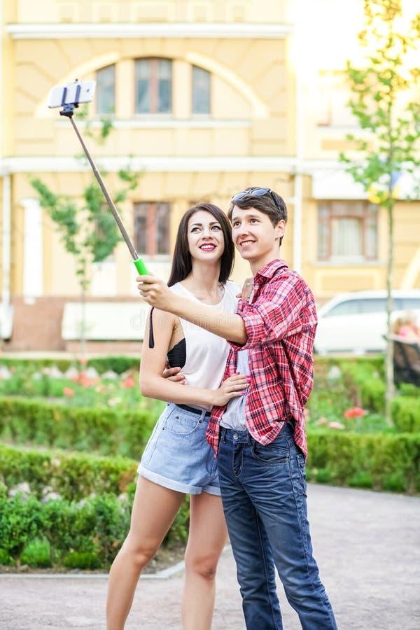 Glückliche junge Touristen verbinden das Nehmen eines selfie mit Smartphone auf dem monopod in der Stadt stockfoto