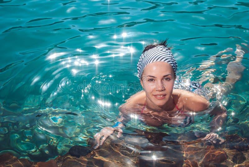 Glückliche, junge und schöne lächelnde Mädchenschwimmen im Meer stockbild