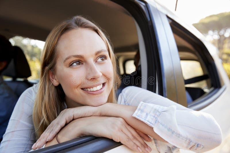 Glückliche junge weiße Frau, die aus einem Autofensterlächeln heraus schaut stockfoto