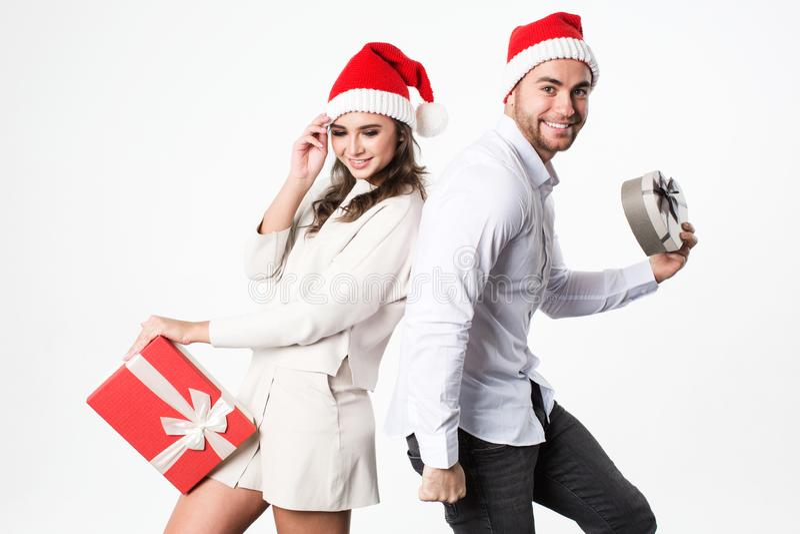 Glückliche junge Weihnachtspaare mit Geschenken auf weißem Hintergrund stockbild