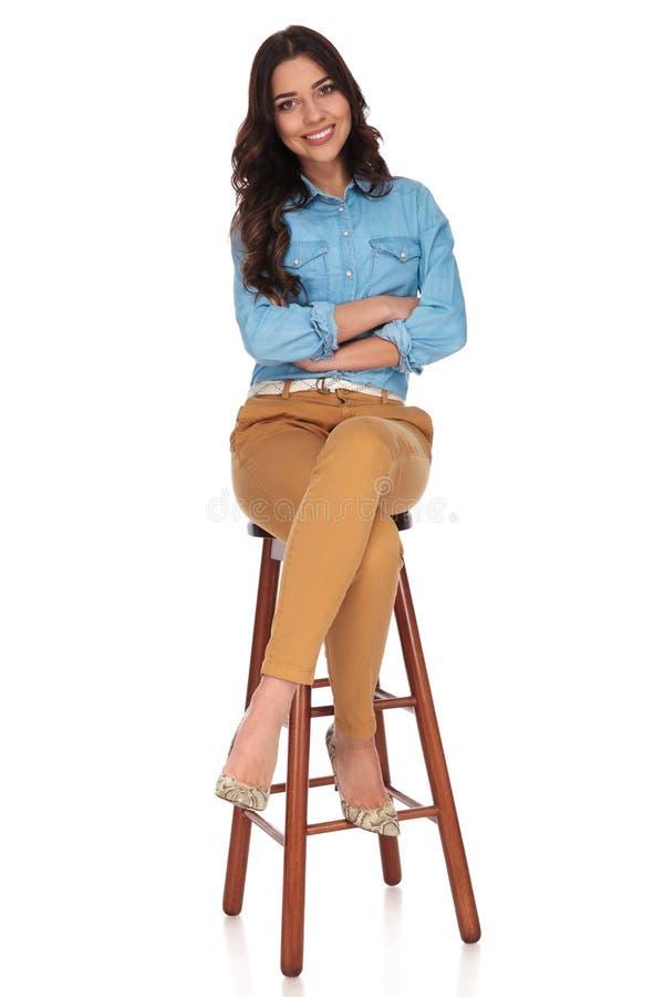 Glückliche junge zufällige Frau, die auf einem Schemel mit den Händen gekreuzt sitzt lizenzfreie stockfotografie