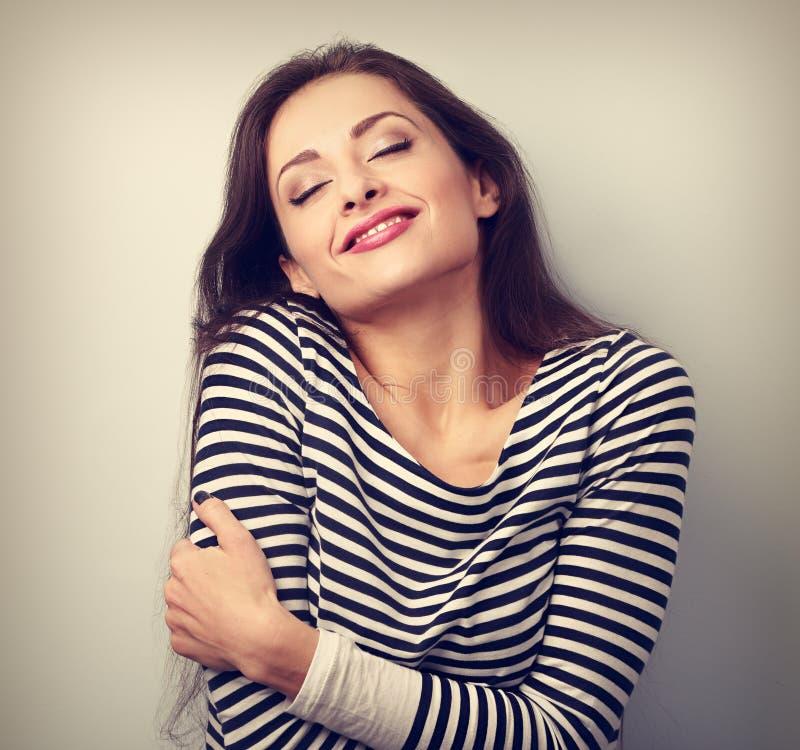 Glückliche junge zufällige Frau, die mit natürlichem emotionalem sich umarmt stockfoto