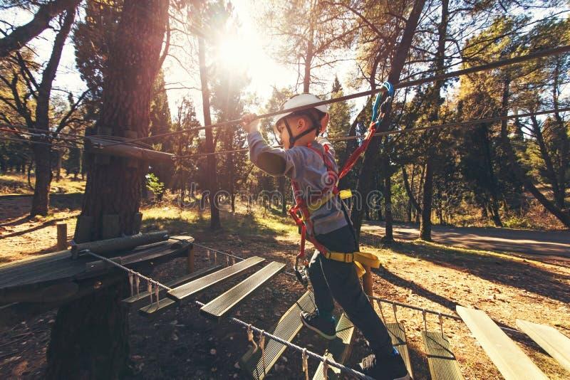 Glückliche Jungen, die am Erlebnispark hält Seile und das Klettern spielen stockfoto