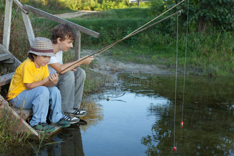 Glückliche Jungen gehen, auf dem Fluss, zwei Kinder zu fischen des fisherma lizenzfreie stockfotos