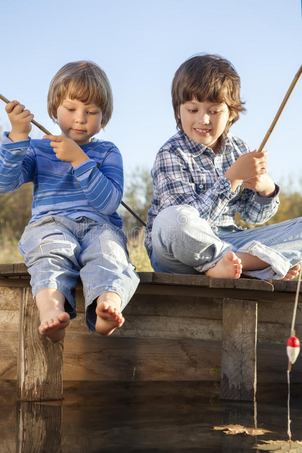 Glückliche Jungen gehen, auf dem Fluss, zwei Kinder zu fischen fisherm stockfoto