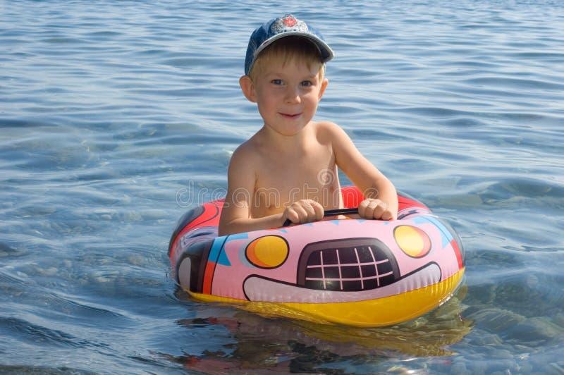 Glückliche Jungenschwimmen lizenzfreies stockbild