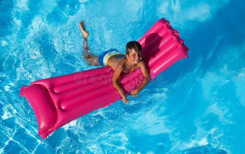 Glückliche Jungenschwimmen auf rosa aufblasbarer Matratze stockfoto