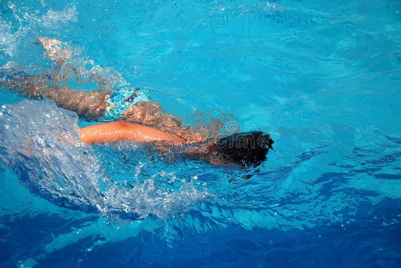 Glückliche Jungenschwimmen im Pool stockfotografie