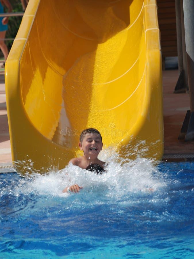 Glückliche Jungenschwimmen im Pool stockfotos