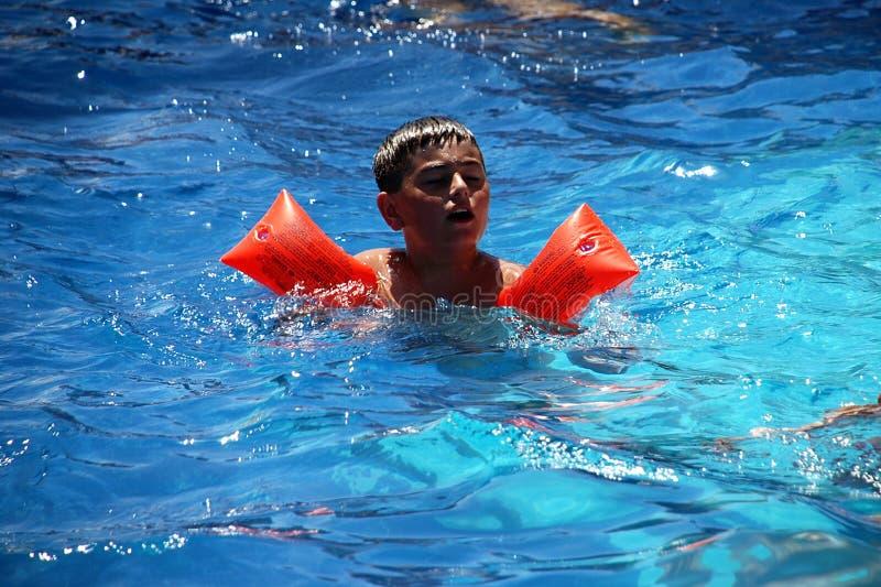 Glückliche Jungenschwimmen im Pool lizenzfreie stockfotos