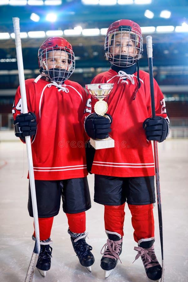 Glückliche Jungenspieler-Eishockey-Siegertrophäe stockfoto
