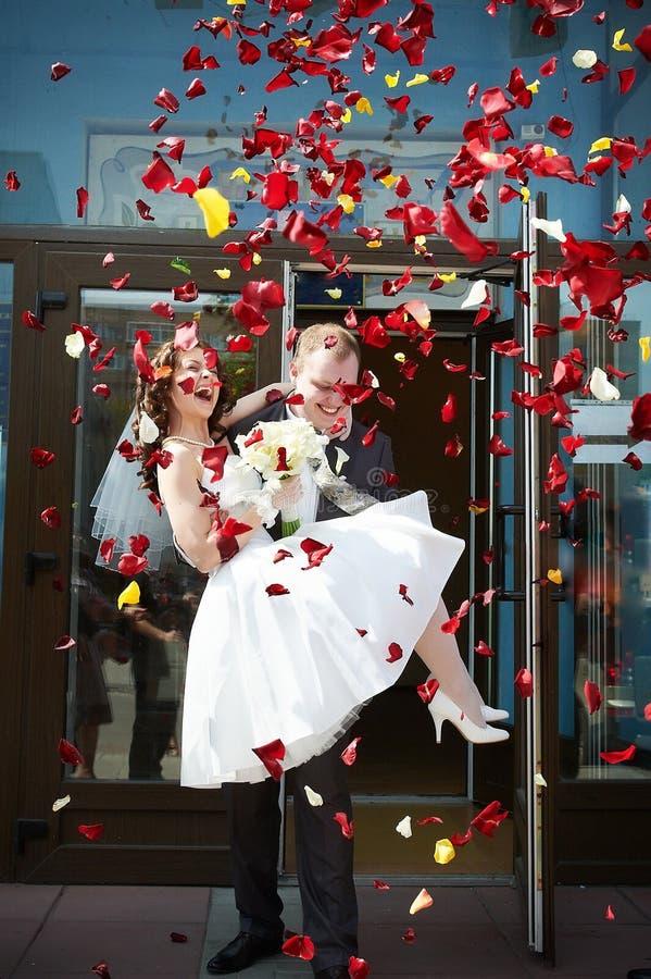 Glückliche Jungvermählten Braut und Bräutigam mit den Blumenblättern stockfoto
