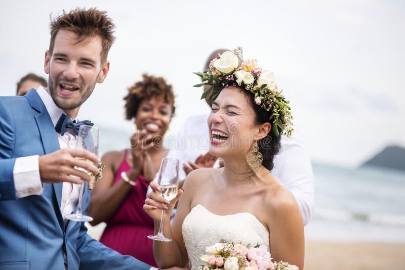 Glückliche Jungvermählten an der Strandhochzeit lizenzfreie stockbilder