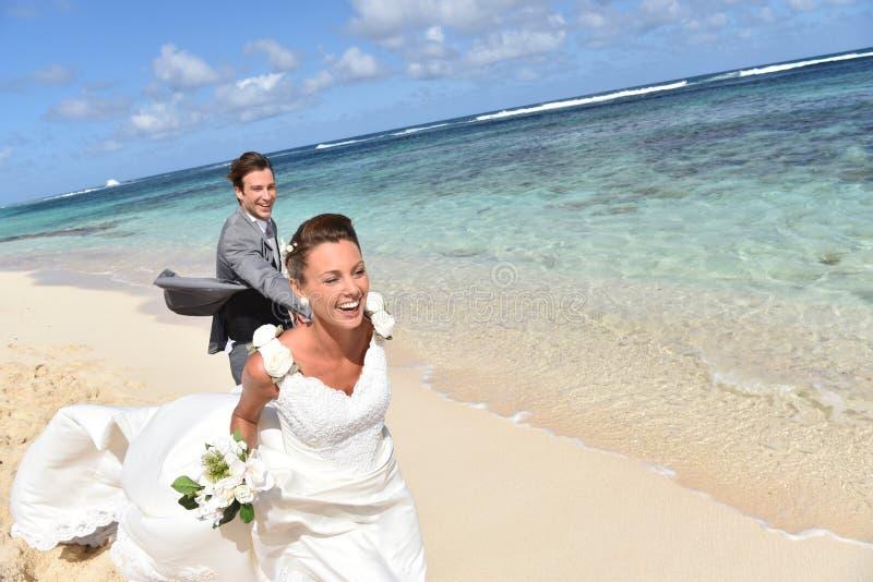 Glückliche Jungvermählten, die auf dem karibischen Strand laufen lizenzfreie stockbilder