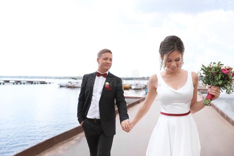 Glückliche Jungvermählten mit schönem Brautblumenstrauß lizenzfreie stockbilder