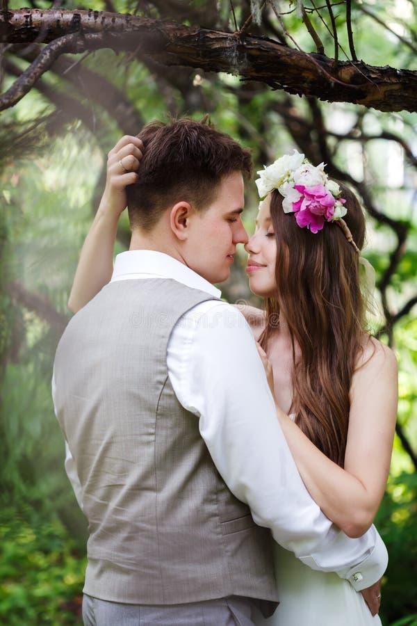 Glückliche Jungvermähltenpaare, die an der Natur aufwerfen stockbild