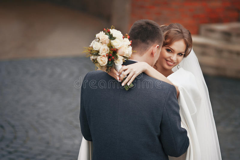 Glückliche Jungvermähltenpaare mit dem Blumenstrauß, der draußen umarmt lizenzfreie stockfotos