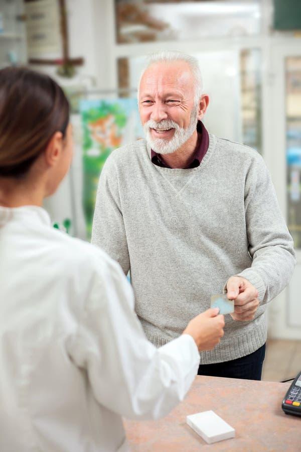 Glückliche kaufende Medikationen des älteren Mannes in einer Apotheke, zahlend mit Kreditkarte stockfoto