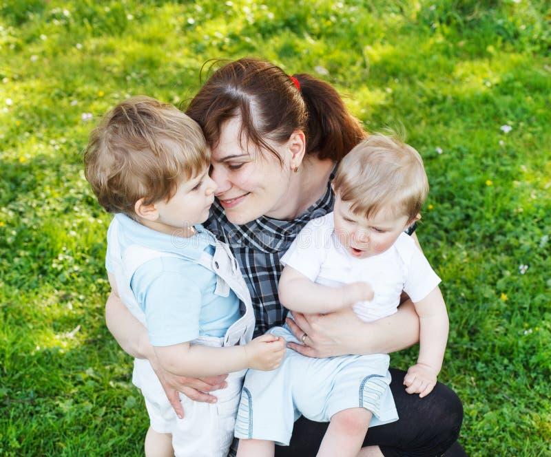 Glückliche kaukasische dreiköpfige Familie: Junge Mutter und zwei wenig sib stockfotografie