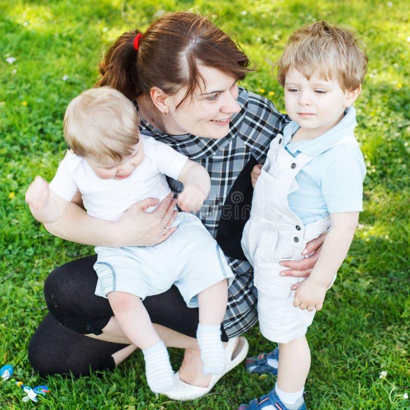 Glückliche kaukasische dreiköpfige Familie: Junge Mutter und zwei wenig sib lizenzfreies stockfoto