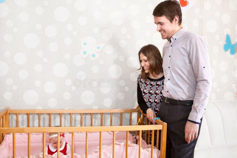 Glückliche kaukasische Eltern, die nahes Babybett stehen und Kind betrachten stockbilder
