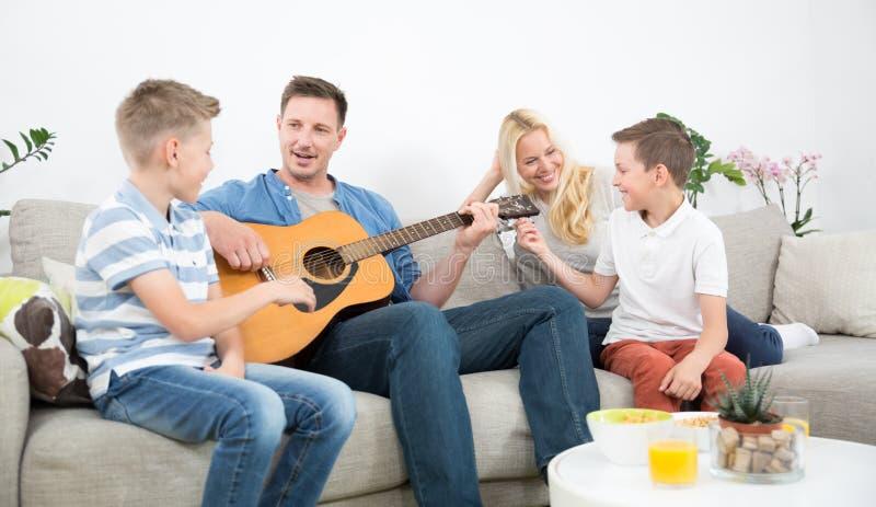 Glückliche kaukasische Familie, die zusammen Lieder am angenehmen modernen Haus lächelt, spielt Gitarre und singt lizenzfreie stockbilder