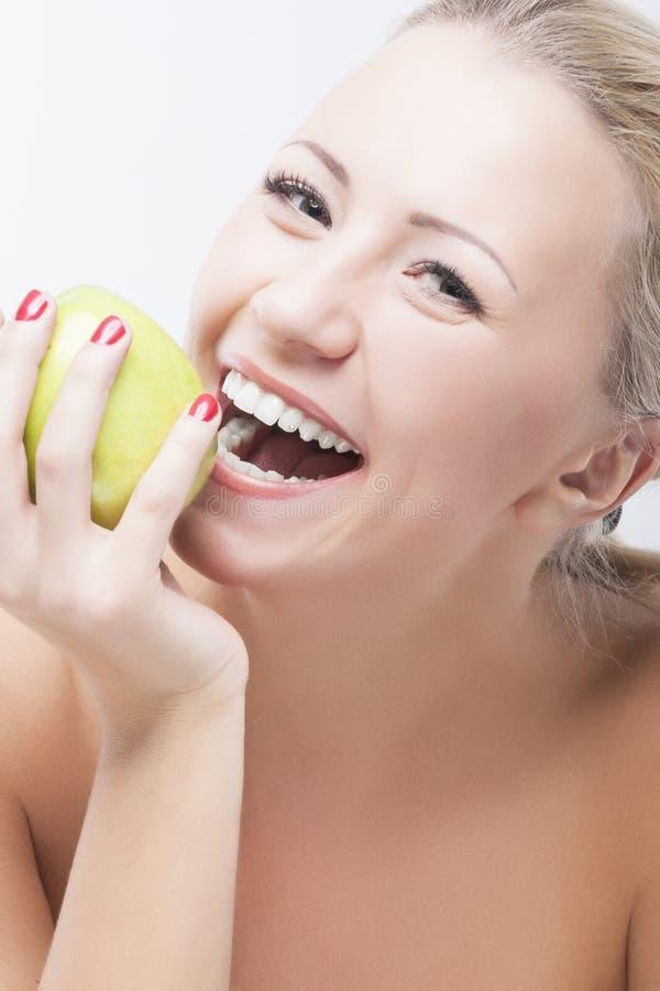 Glückliche kaukasische Frau, die Apple nährt und isst. Gesundes Lifestyl lizenzfreies stockbild