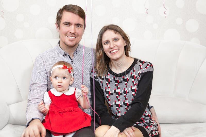 Glückliche kaukasische Leute der Familie drei, die zusammen auf der Couch sitzen lizenzfreie stockfotografie