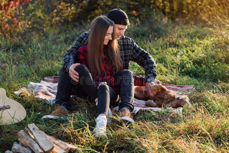 Glückliche kaukasische Paare mit der Gitarre, die im Frühjahr auf Park des Picknicks stillsteht Junger Mann und seine Freundin, d lizenzfreie stockfotos