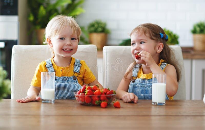 Glückliche Kinder Bruder und Schwester, die Erdbeeren mit Milch essen lizenzfreies stockfoto