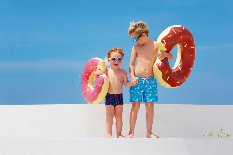 Glückliche Kinder in den Gläsern und Schwimmenstämme mit den Donutgummiringen bereit zu den Sommerferien stockfoto
