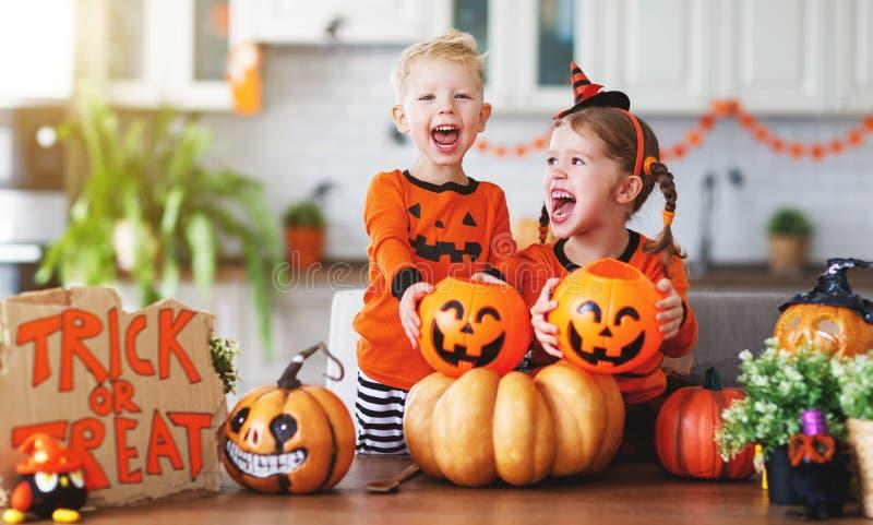 Glückliche Kinder in den Kostümen von Kürbisen bereiten sich nach Hause für h vor stockfotos
