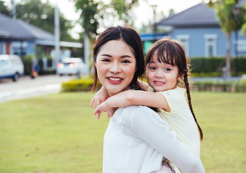 Glückliche Kinder der Familie scherzen den Sohnmädchenkindergarten, der Fahrhintere Doppelpolmuttermutter spielt stockfoto