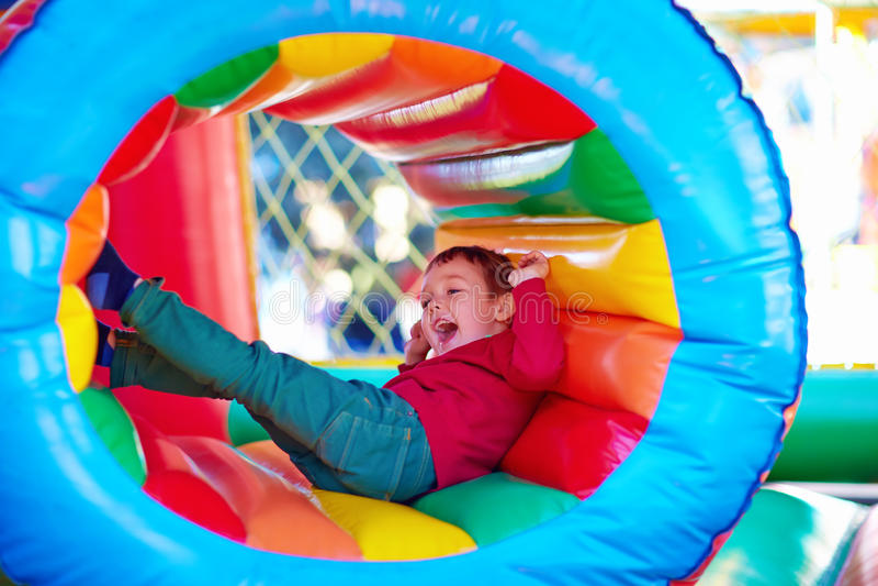 Glückliche Kinder, die auf aufblasbarem Anziehungskraftspielplatz spielen lizenzfreie stockbilder