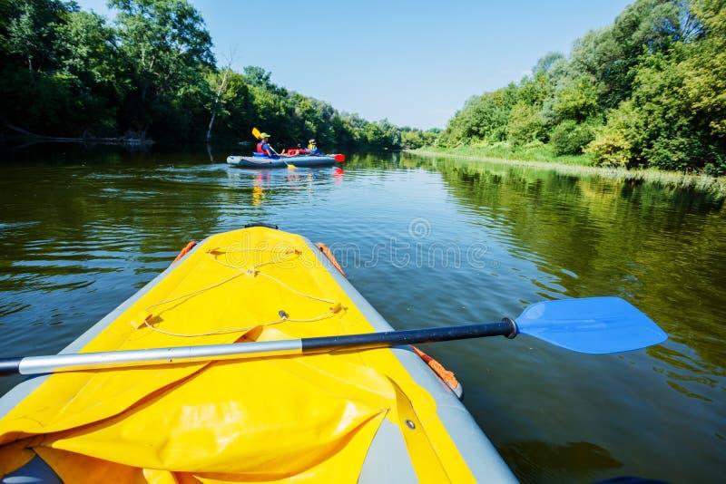 Glückliche Kinder, die auf dem Fluss an einem sonnigen Tag während der Sommerferien Kayak fahren lizenzfreie stockbilder