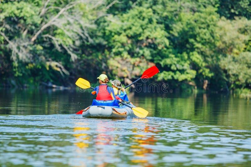 Glückliche Kinder, die auf dem Fluss an einem sonnigen Tag während der Sommerferien Kayak fahren stockfotografie