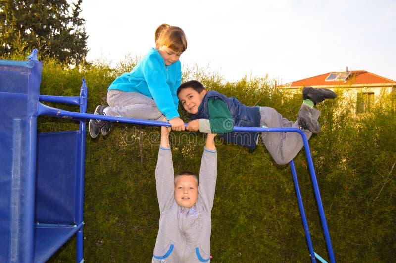 Glückliche Kinder, die auf dem Spielplatz palying sind stockbilder