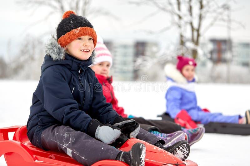 Glückliche Kinder, die auf Schlitten im Winter schieben stockfotografie