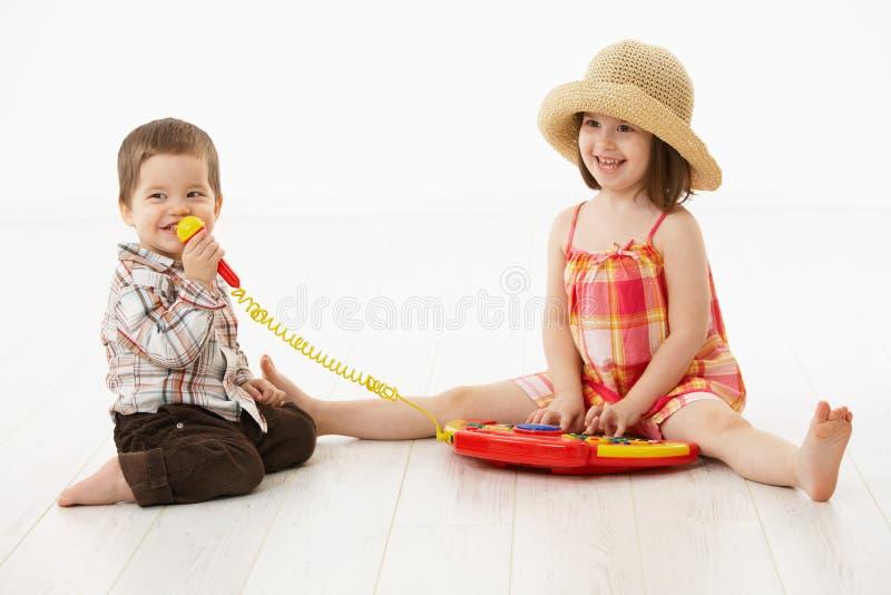 Kleine Kinder, die mit Spielzeuginstrument spielen stockbild