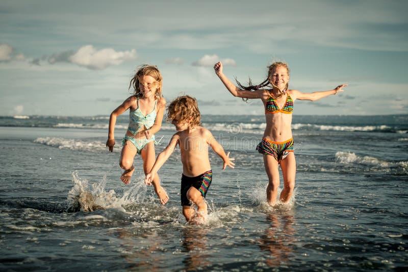 Glückliche Kinder, die auf Strand spielen lizenzfreie stockfotos