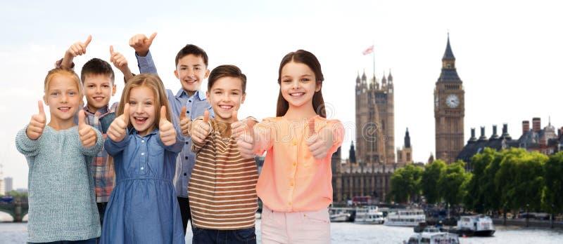 Glückliche Kinder, die Daumen oben über London zeigen lizenzfreies stockbild