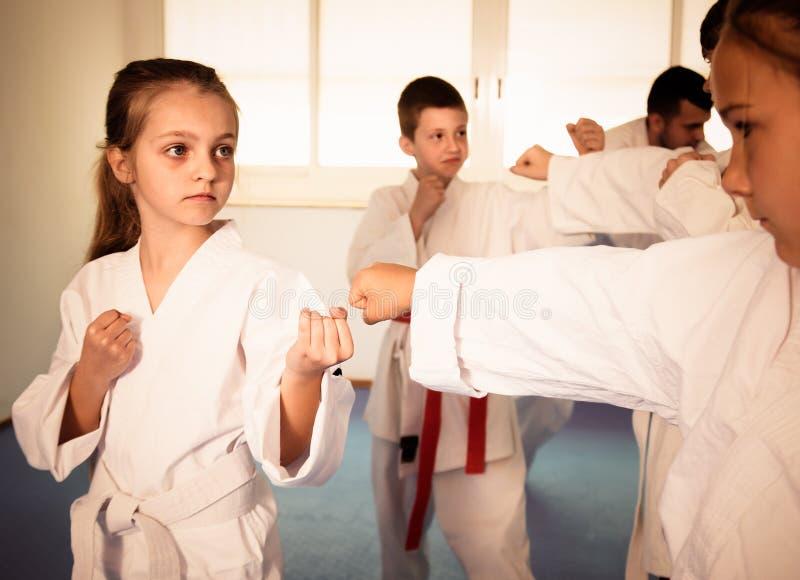 Glückliche Kinder, die in den Paaren in der Karateklasse sich auseinander setzen lizenzfreies stockfoto
