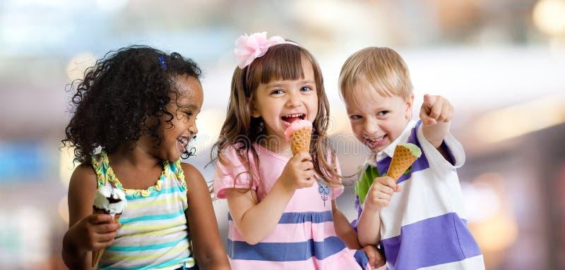 Glückliche Kinder, die Eiscreme an einer Partei im Café essen lizenzfreie stockfotos