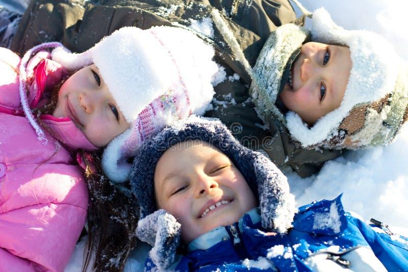 Glückliche Kinder, die im frischen Schnee spielen stockfotografie