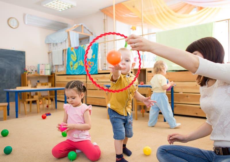 Glückliche Kinder, die mit Ball und Ring im Kindergarten spielen lizenzfreies stockfoto