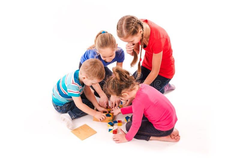 Glückliche Kinder, die mit den Bausteinen lokalisiert auf Weiß spielen lizenzfreie stockbilder